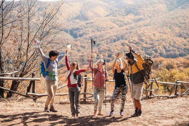 Feliz pequeno grupo de caminhantes em pé na clareira com as mãos no ar no outono. no fundo montanhas e florestas.