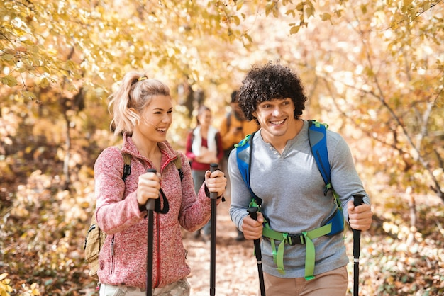 Feliz pequeno grupo de caminhantes que exploram a floresta no outono. em primeiro plano casal andando.