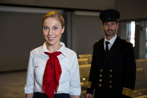 Feliz piloto e aeromoça em pé no terminal do aeroporto