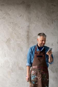 Feliz pintor profissional de meia-idade em roupas de trabalho em pé junto à parede e rolando no smartphone isoladamente