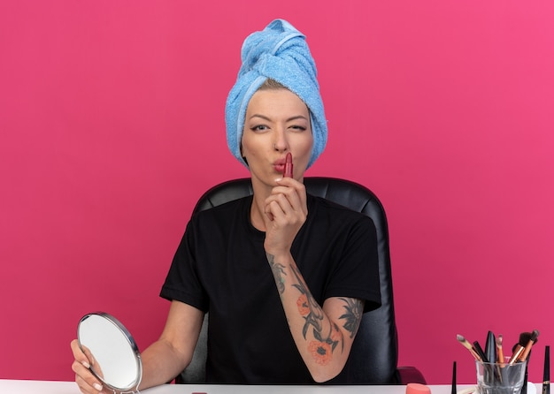 Feliz piscou jovem e linda garota se senta à mesa com ferramentas de maquiagem enroladas no cabelo em uma toalha, aplicando batom isolado na parede rosa