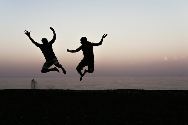 Feliz por dois amigos pulando e pôr do sol na praia.
