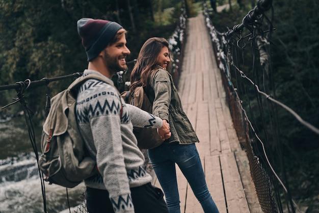 Feliz por estar por perto. lindo casal jovem de mãos dadas e sorrindo enquanto caminha na ponte pênsil
