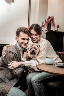 Feliz por estarmos juntos. casal abraçando seu pequeno terrier