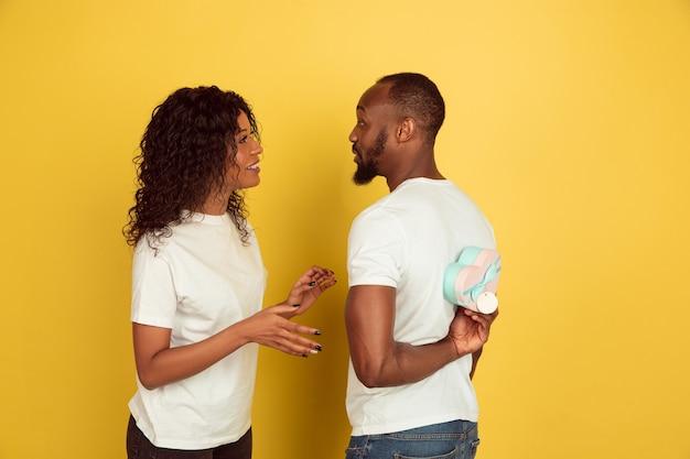 Feliz por receber um presente. celebração do dia dos namorados, feliz casal afro-americano isolado no fundo amarelo do estúdio. conceito de emoções humanas, expressão facial, amor, relações, férias românticas.