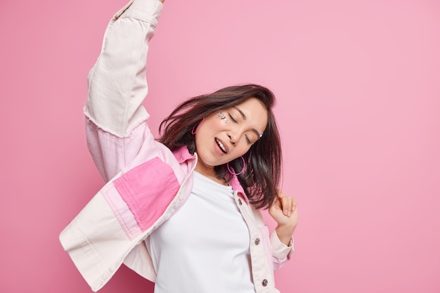 Feliz, positiva, morena, relaxada, mulher, com, aparência oriental, mantém os braços levantados, dança, alegremente, mantém os olhos fechados, desfruta de lazer nos fins de semana, usa roupas elegantes isoladas sobre a parede rosa