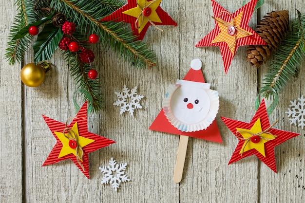 Feliz presente de natal na mesa de madeira papai noel e brinquedos estrela projeto feito à mão das crianças
