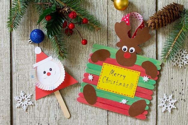 Feliz presente de natal na mesa de madeira papai noel e renas brinquedos artesanato de projeto feito à mão para crianças