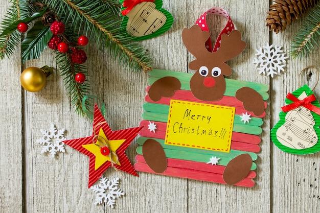 Feliz presente de natal na mesa de madeira rena do papai noel e estrela de brinquedos feito à mão