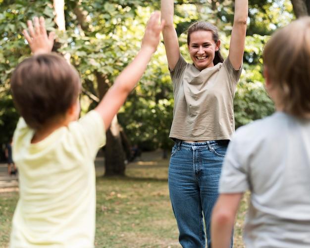 Feliz professor e crianças se exercitando ao ar livre