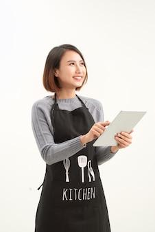 Feliz proprietário de uma pequena empresa com avental segurando um tablet em pé contra um fundo branco