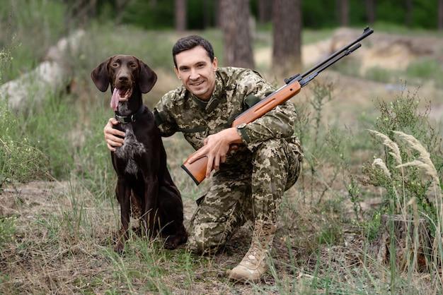 Feliz proprietário do caçador de cão ponteiro com espingarda.