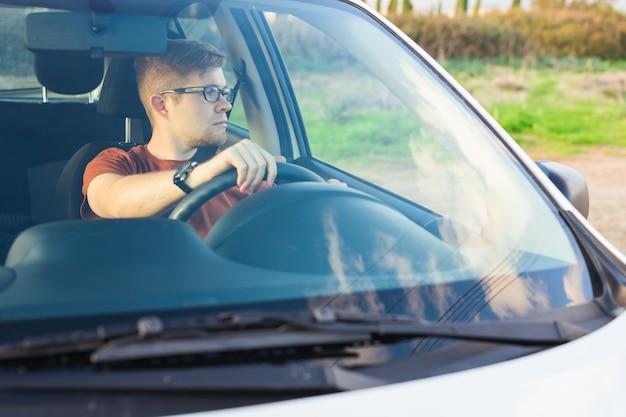 Feliz proprietário. jovem bonito sentado relaxado em seu carro recém-comprado, olhando pela janela.