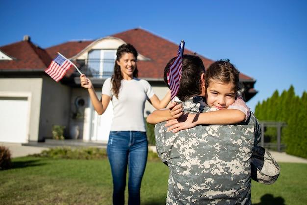 Feliz reencontro de soldado com sua família ao ar livre na frente de sua casa.
