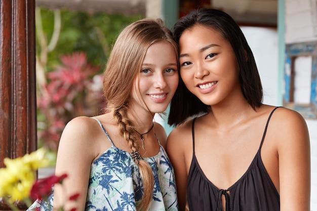 Feliz relaxado e lindas duas mulheres jovens desfrutam da união, passam o tempo de lazer no café oriental, posam para a câmera com expressões encantadas.