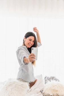 Feliz, retrato, de, um, mulher jovem, levando, selfie, ligado, smartphone