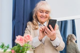 Feliz, retrato, de, um, mulher sênior, usando, telefone móvel