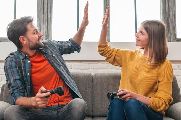Feliz, retrato, de, um, par jovem, sentar sofá, dar, alto, cinco, para, um ao outro, enquanto, videogame jogando