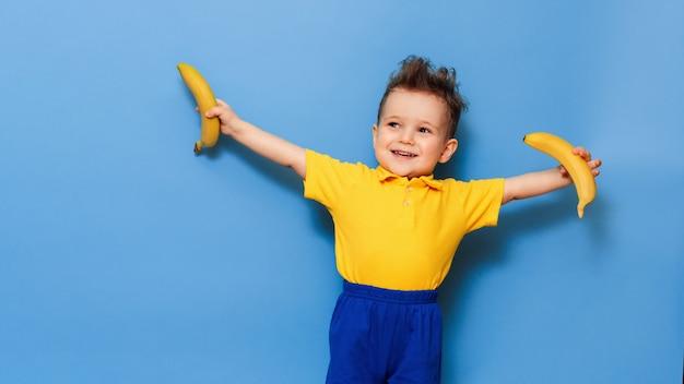 Feliz retrato de uma criança com um sorriso atraente em uma camiseta amarela brincando segurando uma banana isolada em uma parede azul