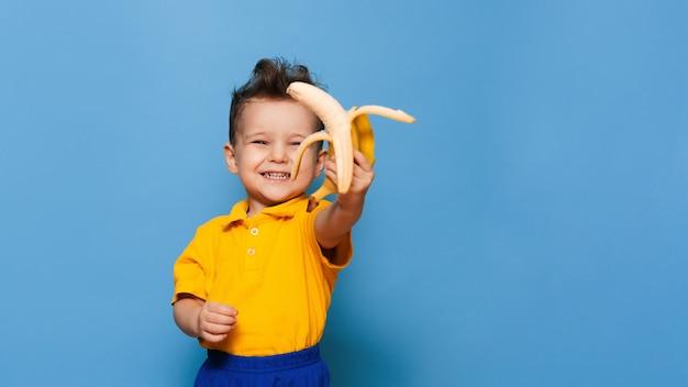 Feliz retrato de uma criança em uma camiseta amarela segurando uma banana descascada sobre fundo azul