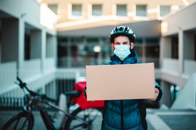Feliz retrato do mensageiro com o pacote a ser entregue. o homem guarda a máscara protetora para o trabalho. fundo de bicicleta. entrega em domicílio, transportador, vírus