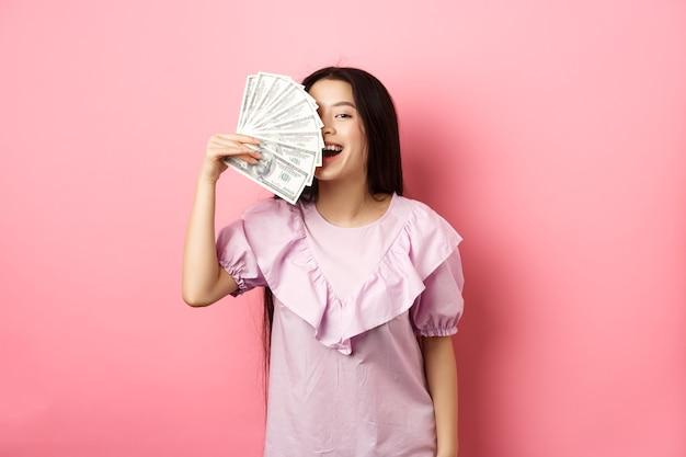 Feliz rica mulher asiática mostrando dinheiro e sorrindo, fazendo compras com dinheiro, em um vestido contra o fundo rosa.