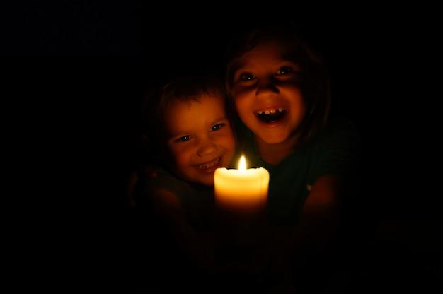 Feliz rindo crianças irmãos menino e menina admira uma vela acesa de cera à noite em casa