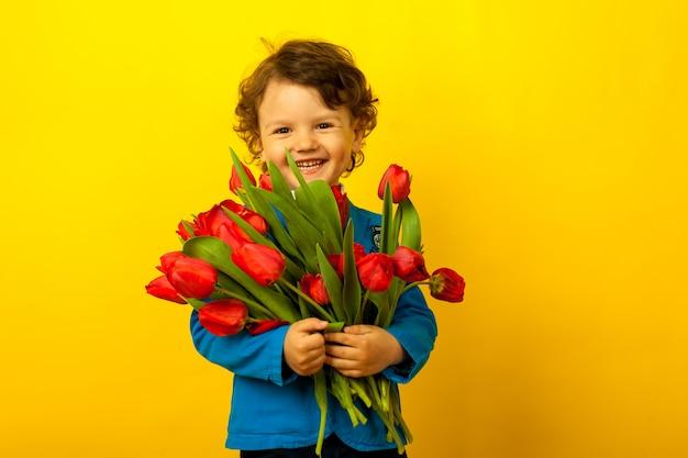 Feliz rindo menino criança encaracolado com um buquê de tulipas vermelhas nas mãos