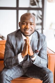Feliz rindo rico empresário americano africano bem sucedido magnata gesto de mãos postas em elegante e ...