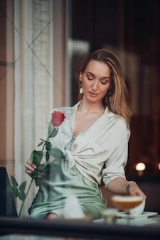 Feliz romântica jovem linda com uma flor rosa vermelha, sonhando sentada em um café durante o namoro dia dos namorados