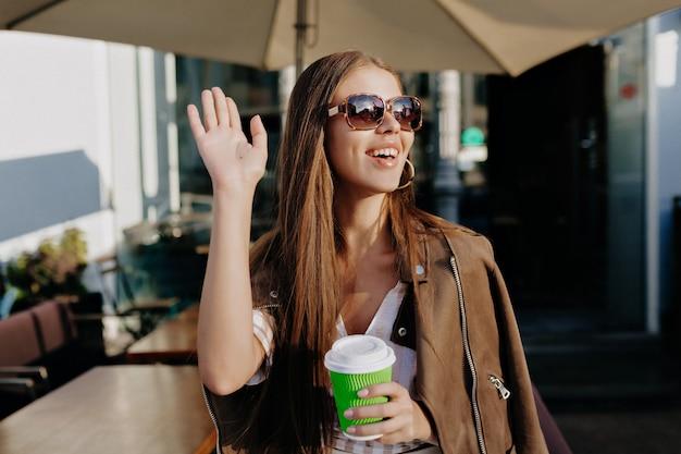 Feliz saiu garota de cabelos escuros olhando para trás, em pé na velha rua pela manhã, bebe café e acenando para alguém. muito jovem com jaqueta de couro, esperando um amigo na avenida.
