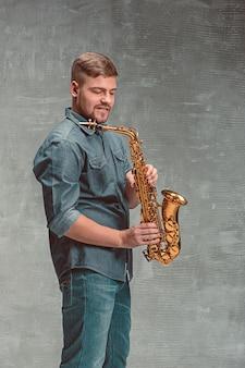 Feliz saxofonista com saxofone sobre fundo cinza