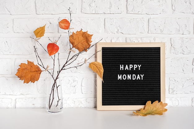 Feliz segunda-feira texto no quadro de letra preto e buquê de ramos com folhas amarelas em prendedores de roupa em um vaso na mesa
