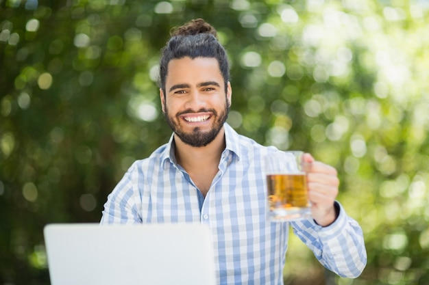 Feliz, segurando o copo de cerveja em um restaurante