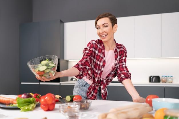 Feliz segurando um grito de salada, jovem dona de casa corta tomate, pepino e pimenta para um jantar em família ou
