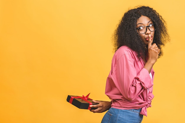 Feliz senhora afro-americana casual olhando para o lado e rindo enquanto segura um presente