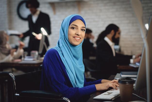 Feliz senhora árabe em cadeira de rodas trabalha no computador.