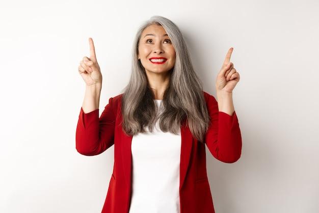Feliz senhora asiática de blazer vermelho e maquiagem, olhando e apontando os dedos para cima, mostrando a oferta especial, em pé sobre um fundo branco.