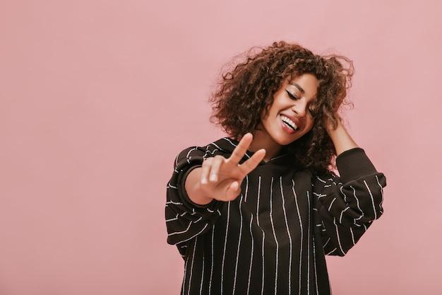 Feliz senhora de cabelos cacheados com maquiagem legal em roupas listradas elegantes, mostrando o símbolo da paz e sorrindo com os olhos fechados na parede rosa.