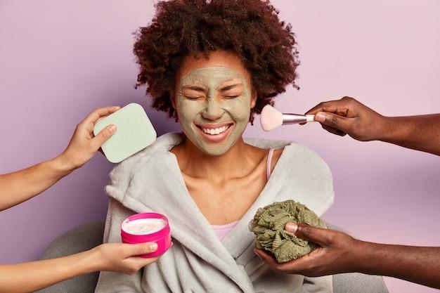Feliz senhora de cabelos cacheados em roupão de banho recebendo tratamentos anti-envelhecimento e de beleza ao mesmo tempo