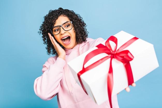 Feliz senhora encaracolada afro-americana no riso casual, segurando a caixa de presente presente isolada sobre fundo azul.