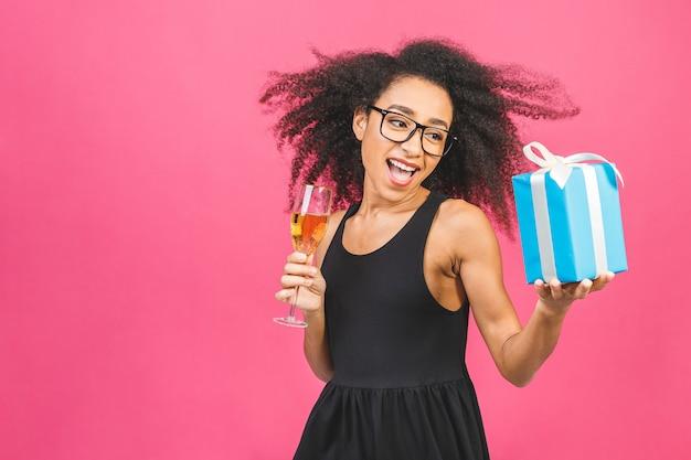 Feliz senhora encaracolada no riso casual, segurando um presente e bebendo uma taça de champanhe rosa.