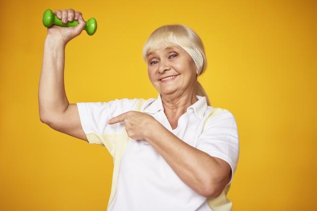 Feliz senhora idosa fazendo exercício de halteres bíceps