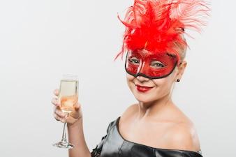 Feliz, senhora jovem, em, máscara, com, vermelho, penas, vidro segurando