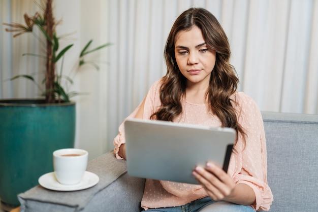 Feliz senhora latina relaxar bebendo café em casa sozinho sentar na sala usando o tablet digital.
