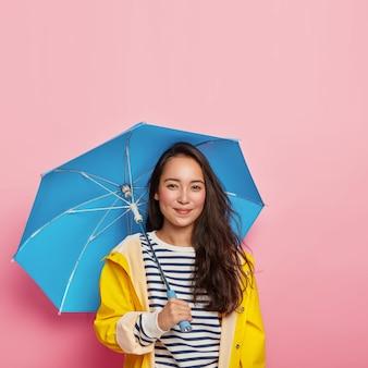 Feliz senhora oriental de cabelos escuros com beleza natural, se sente seca e protegida, usa capa de chuva impermeável, carrega guarda-chuva, aproveita o tempo livre durante o dia chuvoso de outono