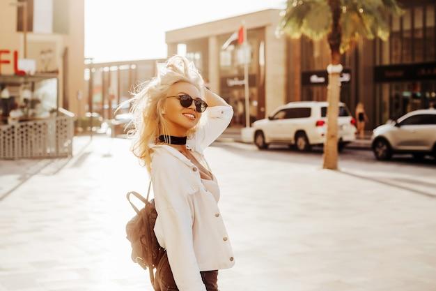 Feliz senhora russa na cidade urbana emirados estilo de vida com a famosa palmeira do país do golfo. senhora fotografia feroz na rua do lugar turístico.
