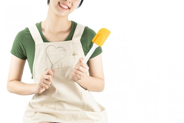Feliz senhora segurando coisas de cozinha sobre fundo de espaço de cópia