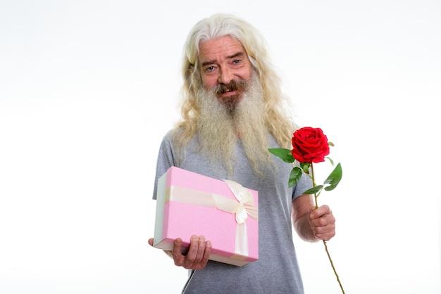 Feliz sênior barbudo sorrindo enquanto segura um presente