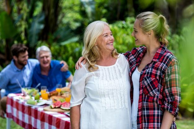 Feliz sogra e nora em pé no quintal